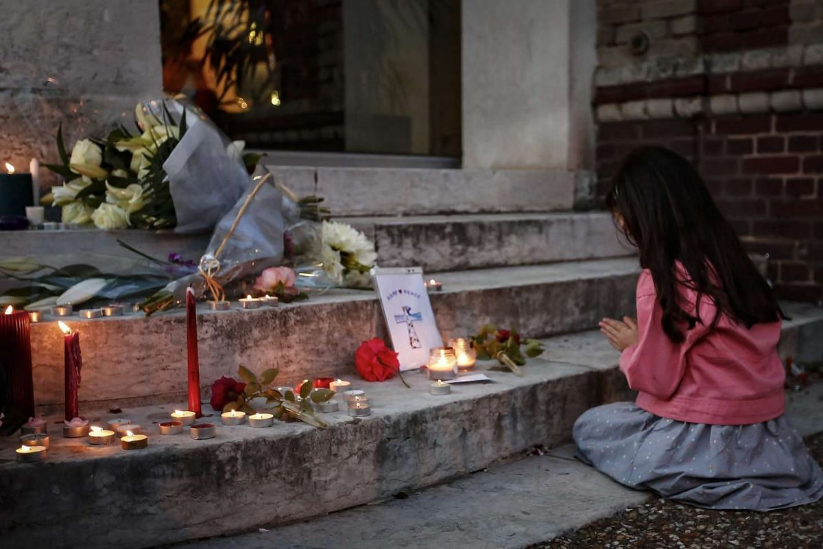 A girl prays at a makeshift memorial in front of the city hall after a fatal hostage-taking incident at the church in Saint-Etienne-du-Rouvray, near Rouen, France, July 26, 2016. PHOTO: EPA