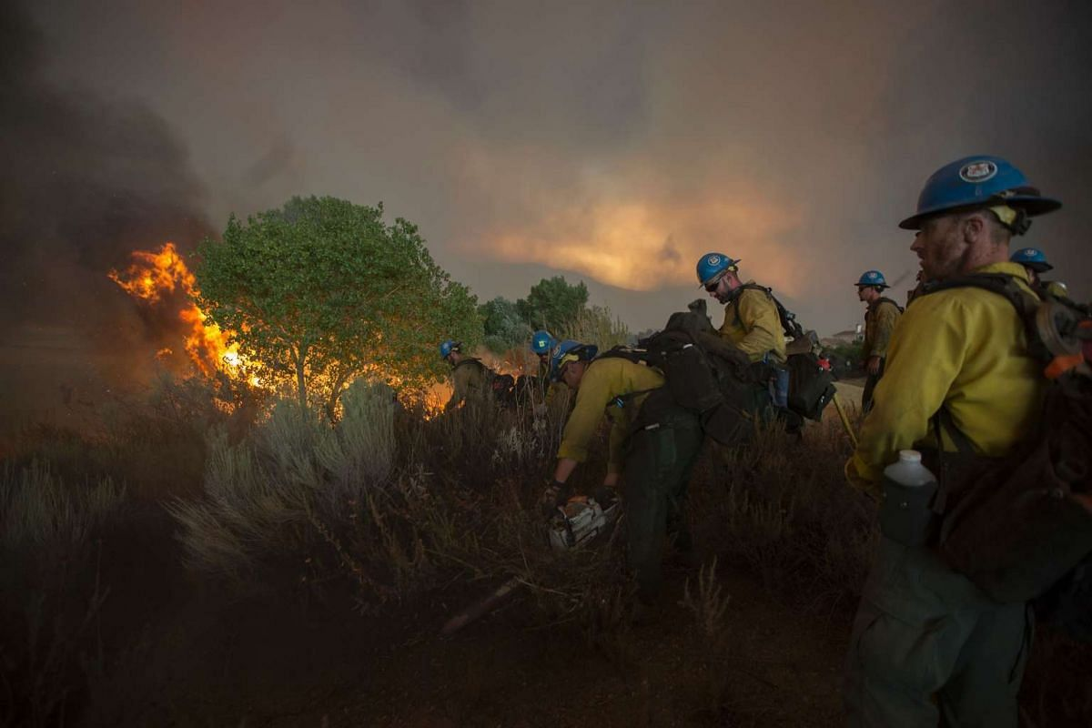 Firefighters of the Texas Canyon Hotshot crew fight the Sand Fire on July 23, 2016 near Santa Clarita, California.