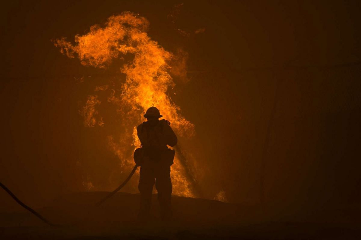 A firefighter hoses down burning pipes near a water tank at the Sand Fire on July 23, 2016 near Santa Clarita, California.