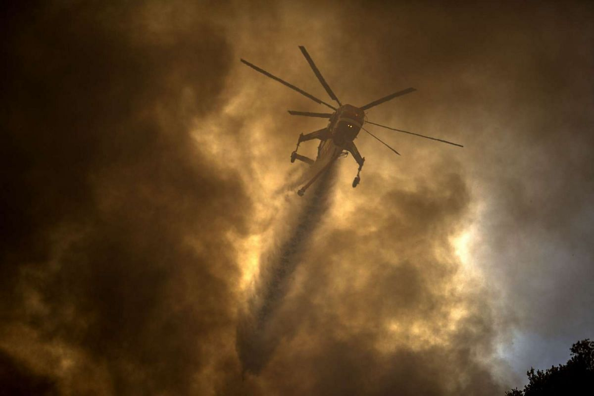 A firefighting helicopter makes a water drop near homes at the Sand Fire on July 24, 2016 in Santa Clarita, California.