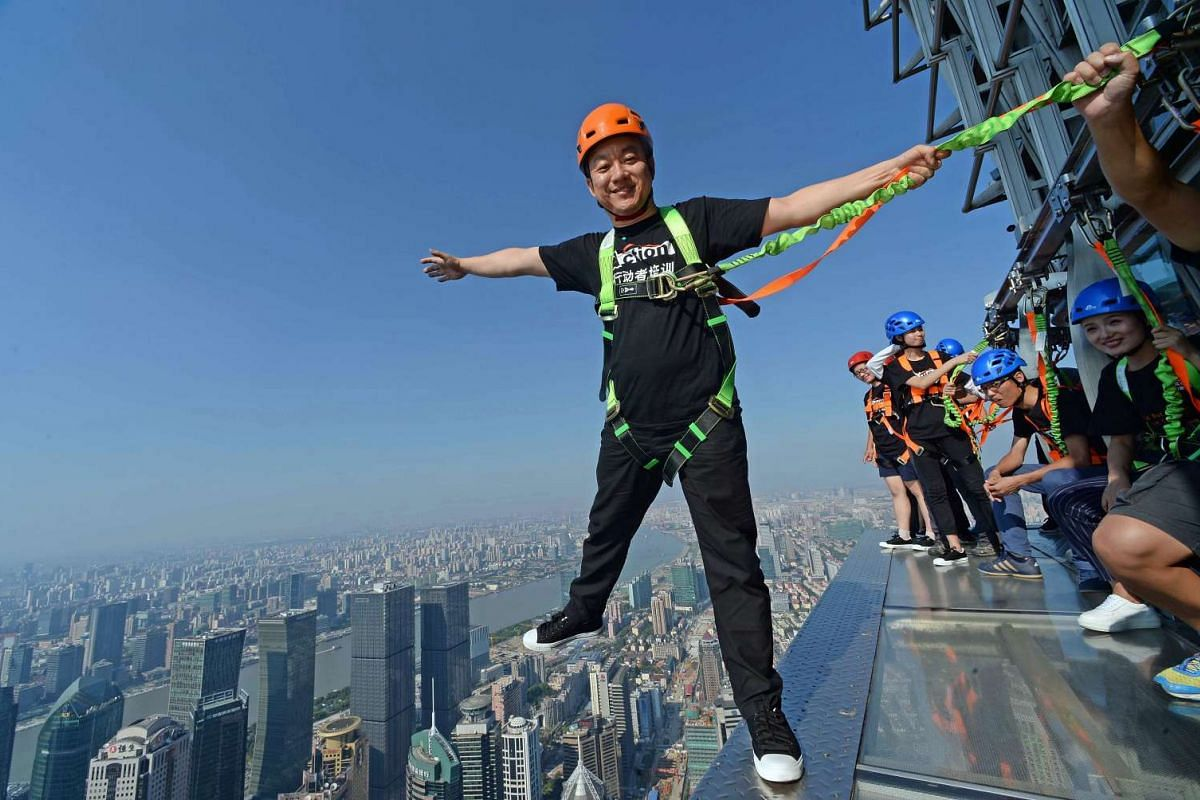 In a photo release today July 28, 2016,  a visitor (L) balances on an open-air glass walkway with other visitors outside the 88th floor of Jinmao Tower in the Lujiazui area of Shanghai on July 25, 2016. The 60-metre long and 1.2-meter wide walkway is