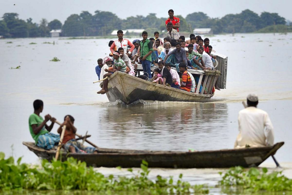 Flood affected villagers travel in county boats as an entire area is submerged in flood waters in the flood affected Morigaon district of Assam state, India, July 27, 2016. PHOTO: EPA