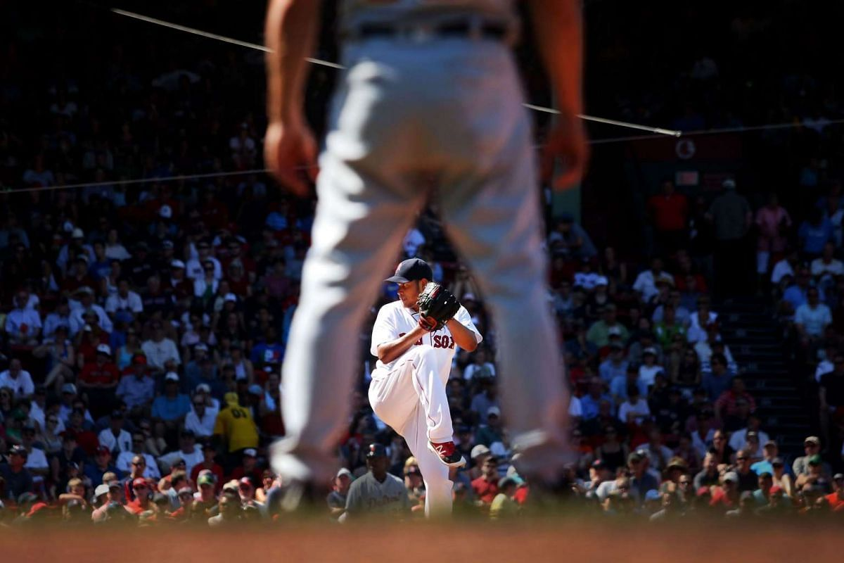 Eduardo Rodriguez #52 of the Boston Red Sox delivers as seen through the legs of Detroit Tigers first base coach Omar Vizquel #13 in the sixth inning during the game at Fenway Park on July 27, 2016 in Boston, Massachusetts. PHOTO: GETTY IMAGES/AFP