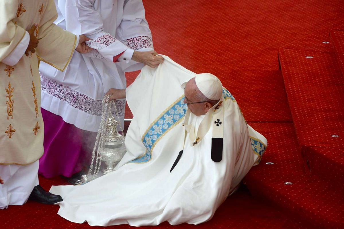 Pope Francis is helped onto his feet after falling down the stairs during a mass at the Jasna Gora Monastery in Czestochowa, Poland, on July 28, 2016.