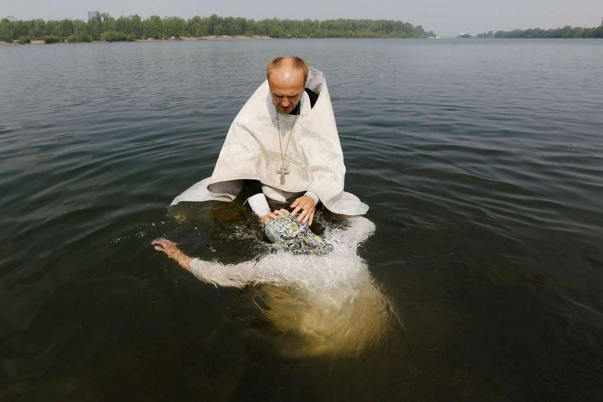 An orthodox priest baptises a woman in the Yenisei river at a ceremony marking the Christianisation of the country in Krasnoyarsk, Siberia, Russia, on July 28, 2016.