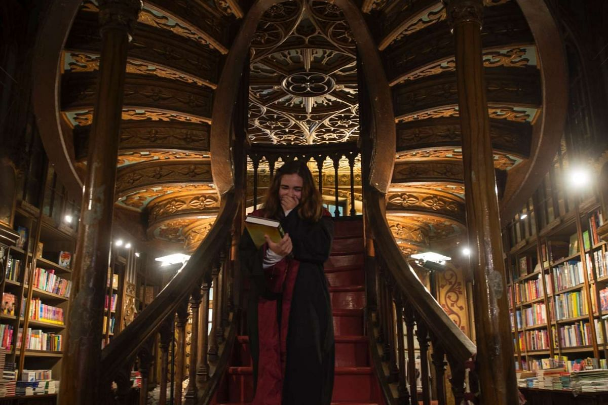 Portuguese Patricia Camarada gestures after purchasing the first copy of British author J.K. Rowling's latest book in the Potter series, Harry Potter and the Cursed Child, on July 31 at Lello, a Gothic Revival style bookstore in the historic centre