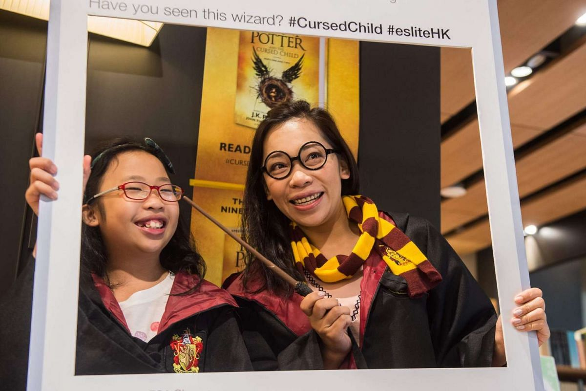 A mother and her daughter pose dressed up as Harry Potter characters in front of a poster advertising the new book Harry Potter and the Cursed Child on the day of its release at a bookstore in Hong Kong on July 31, 2016.