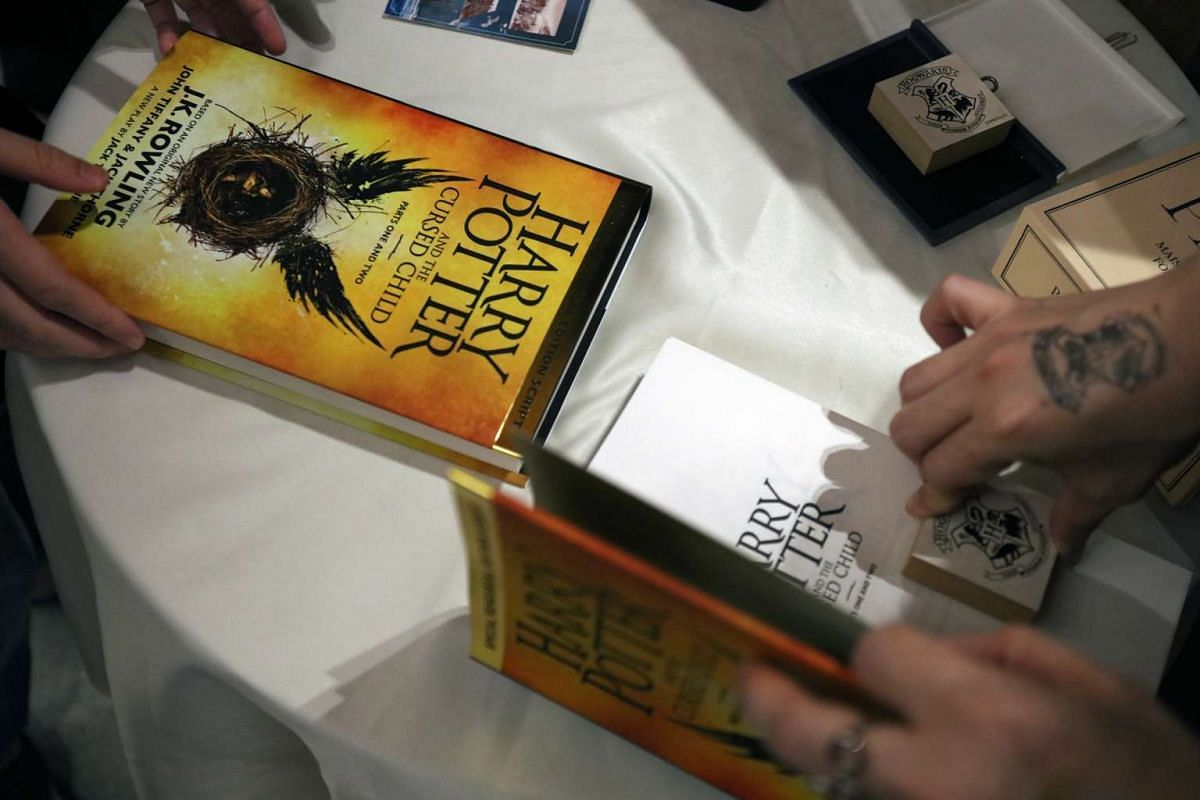 Customers getting their copies of the new Harry Potter book stamped with a design bearing the logo of the different houses at Kinokuniya bookstore in Singapore on July 31.