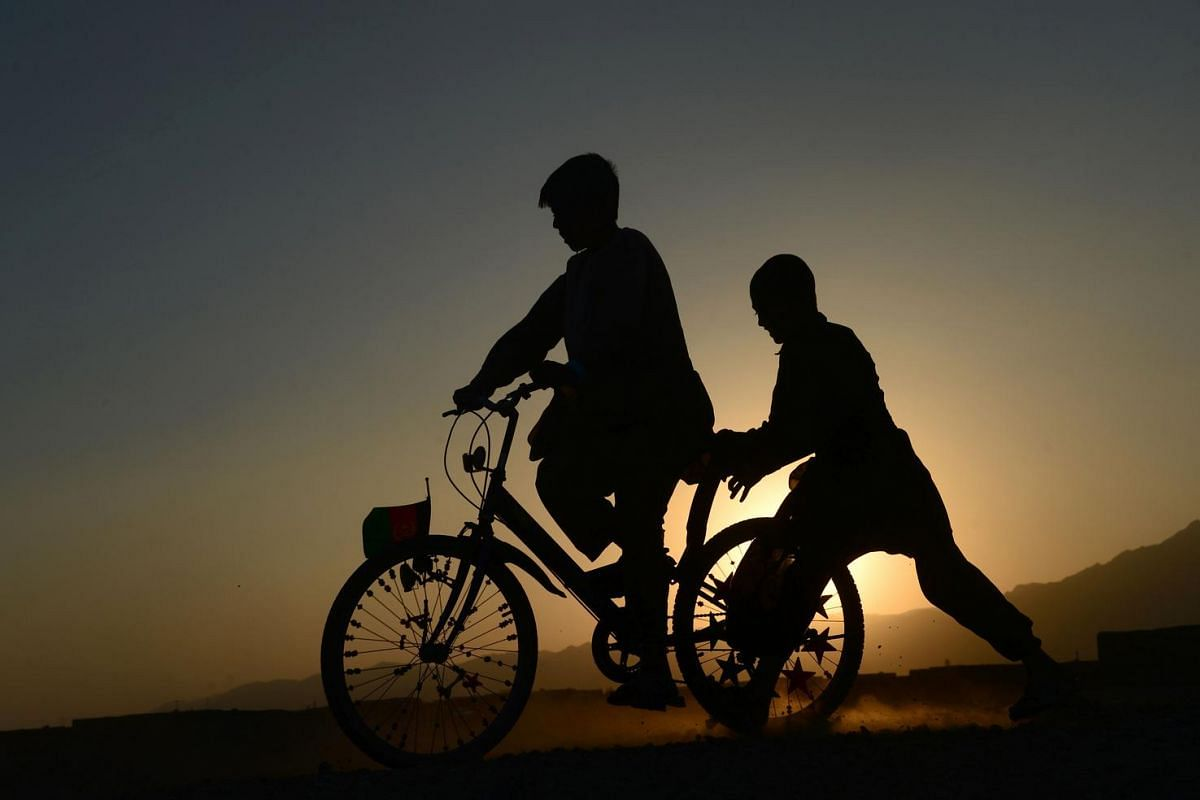 Afghan children ride a bike along a road during sunset on the outskirts of Herat on July 30.