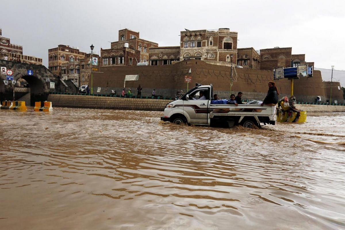A Vehicle drives through a flooded road following heavy rains in the old city of Sana'a, Yemen, July 31. Torrential rain hit Sana'a and most parts of Yemen as summer temperatures soar.