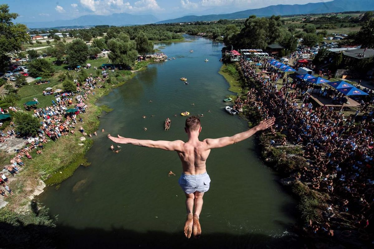 People look at a man as he jumps from the 22 meters high bridge Ura during the High Diving competition near the town of Gjakova on July 31.