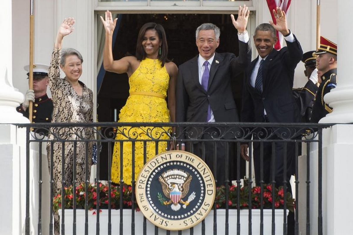 US President Barack Obama (right), First Lady Michelle Obama (third from right), Singapore's Prime Minister Lee Hsien Loong and his wife wave during a State Arrival ceremony on the South Lawn of the White House in Washington, DC on Aug 2, 2016.