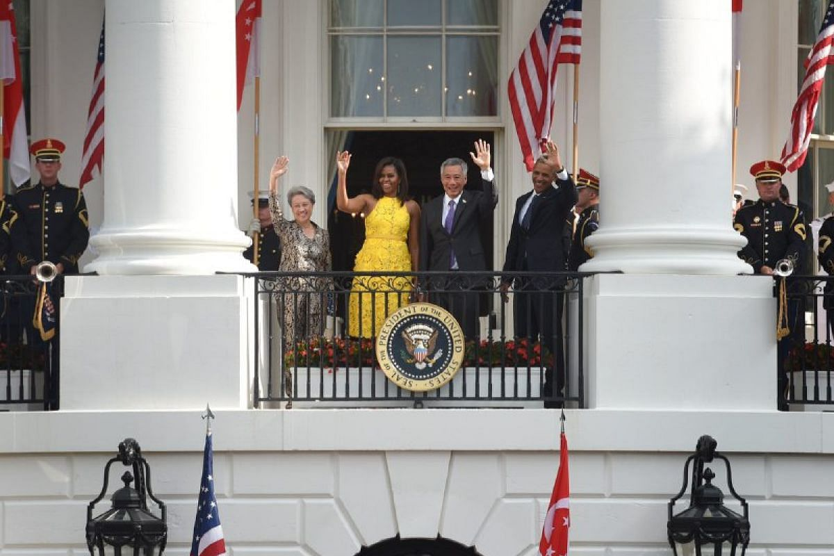 US President Barack Obama (right), First Lady Michelle Obama (second from left), Prime Minister Lee Hsien Loong (second from right) and his wife wave during a State Arrival ceremony on the South Lawn of the White House in Washington, DC, on August 2.