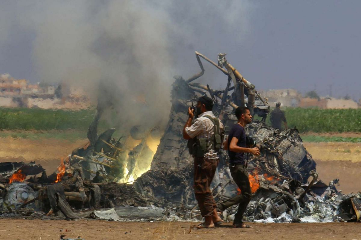 Men inspect the wreckage of a Russian helicopter that had been shot down in the north of Syria's rebel-held Idlib province, Syria, on Aug 1, 2016.