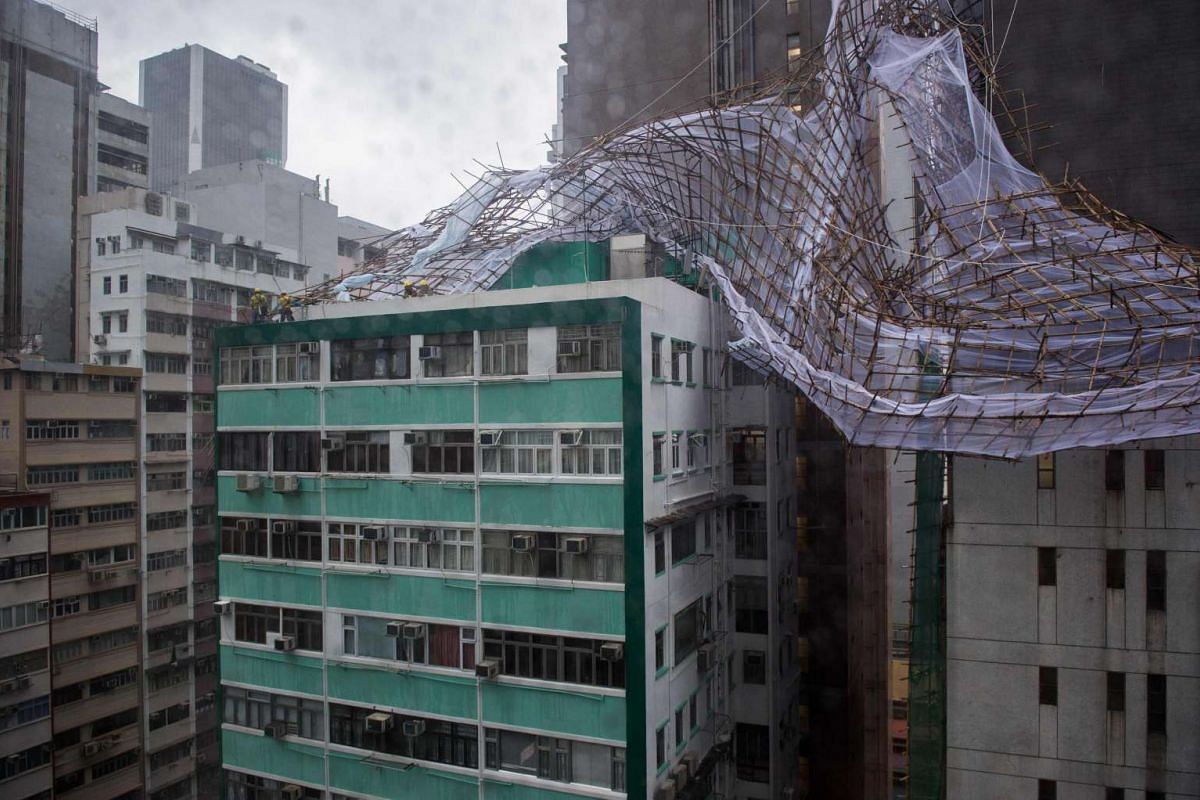 "Rescue workers attempt to secure bamboo scaffolding that was damaged overnight at the top of a building in Hong Kong on Aug 2, 2016, during a ""T8"" storm signal raised for Typhoon Nida."