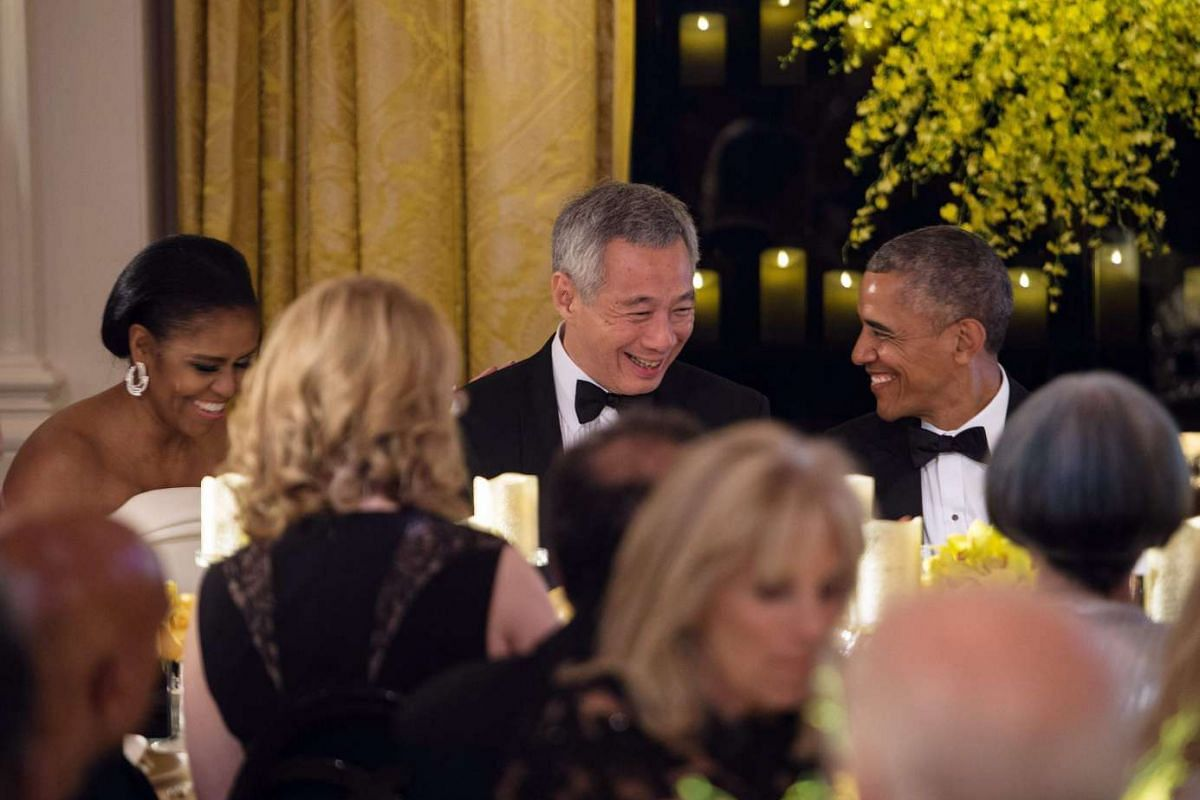 Singapore's Prime Minister Lee Hsien Loong (centre) chats with US President Barack Obama (right) and First Lady Michelle Obama during a state dinner in his honor at the White House in Washington, DC, on August 2, 2016.