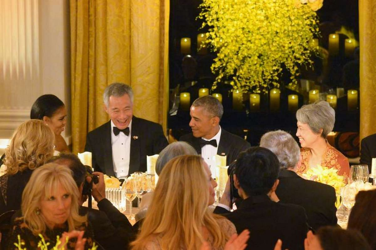 Prime Minister Lee Hsien Loong (centre) chats with US President Barack Obama (right) and First Lady Michelle Obama during a state dinner in his honour at the White House in Washington, DC on Aug 2, 2016.