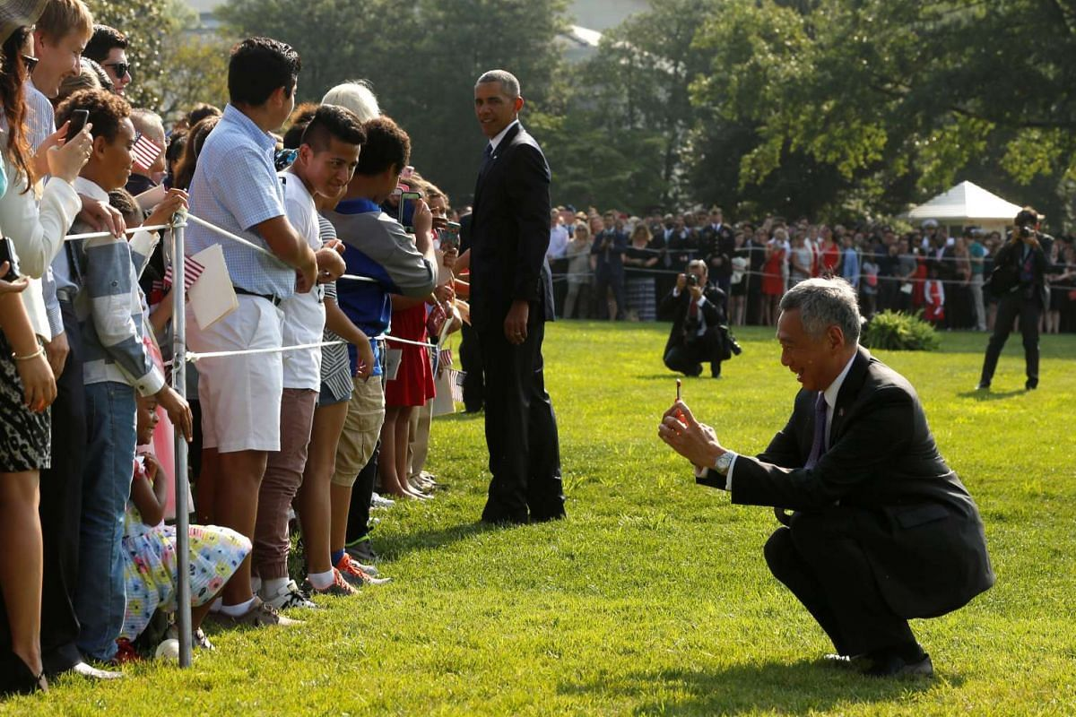 PM Lee Hsien Loong stooping to take a picture as he and US President Barack Obama greet visitors on the South Lawn of the White House in Washington, DC on August 2..