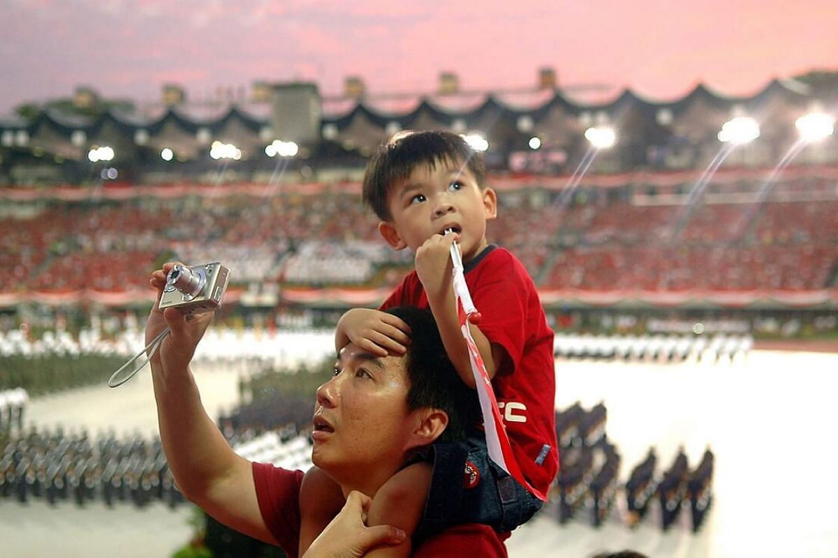 2006: There was much to see during the parade, with this man training his camera in one direction while the little boy perched on his shoulders was drawn to something else.