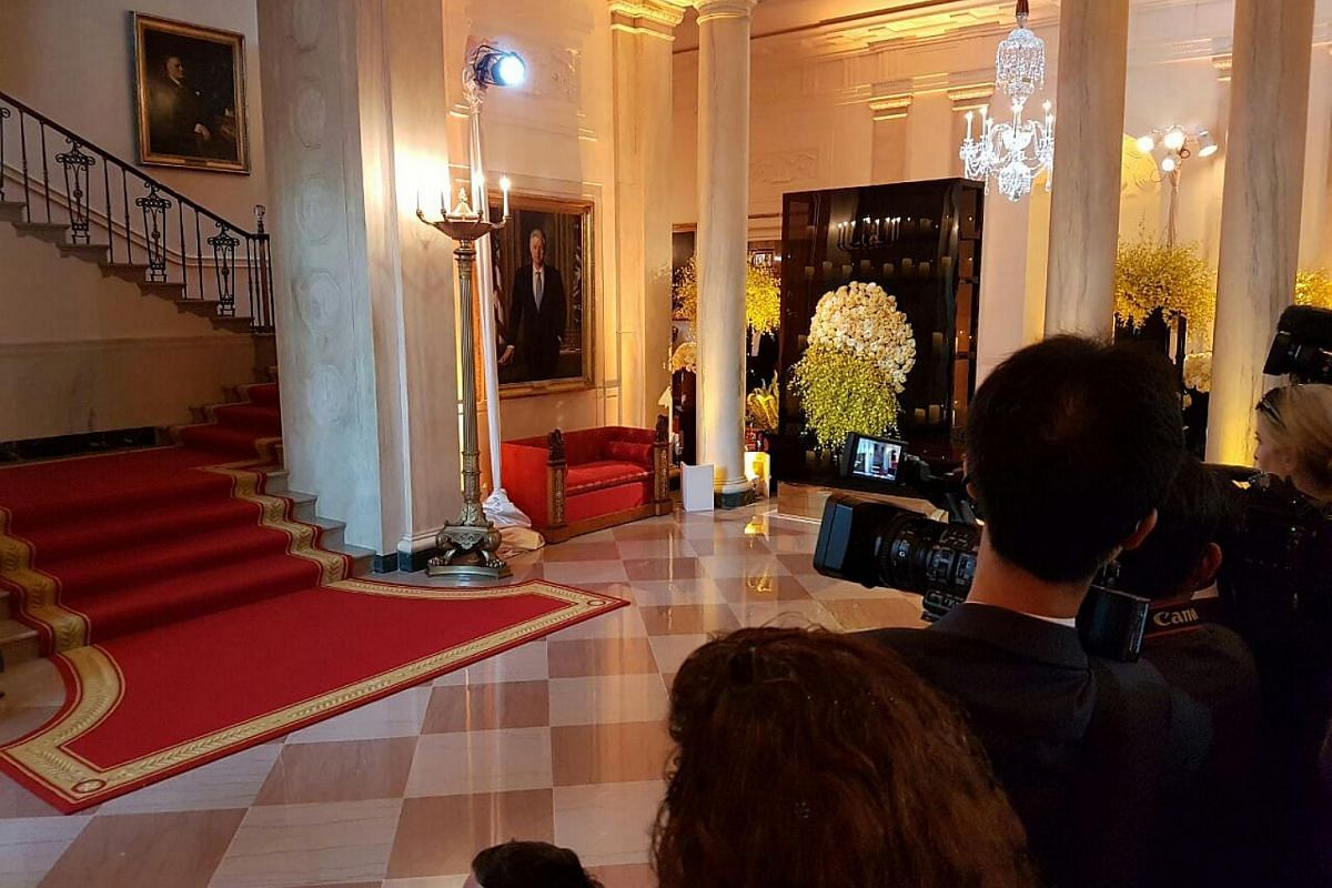 Members of the media waiting for the guests in the grand foyer of the White House. Yellow orchids and yellow and white roses are part of the decorations, symbolising the friendship between the two nations.