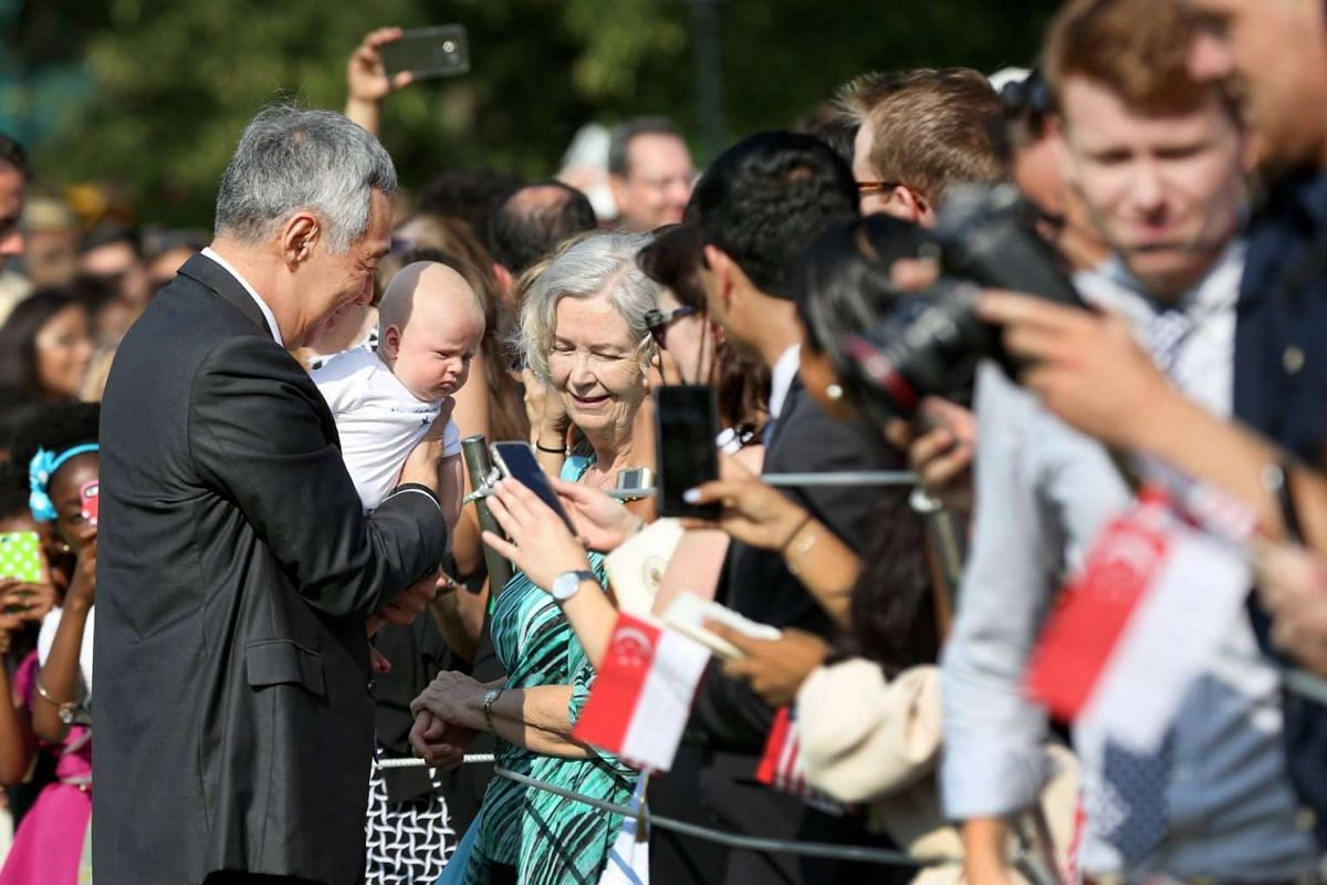 Singapore Prime Minister Lee Hsien Loong holds a baby during the arrival ceremony welcoming him and his wife to the White House on Aug 2, 2016.