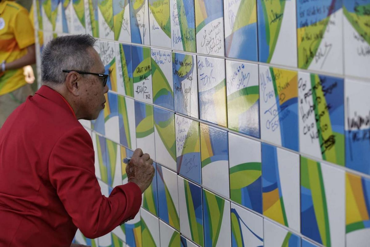 Mr Low Teo Ping, chef de mission of Team Singapore, penning his well-wishes on a wall during the welcome ceremony at the Olympic Village in Rio de Janiero, Brazil, on August 2.