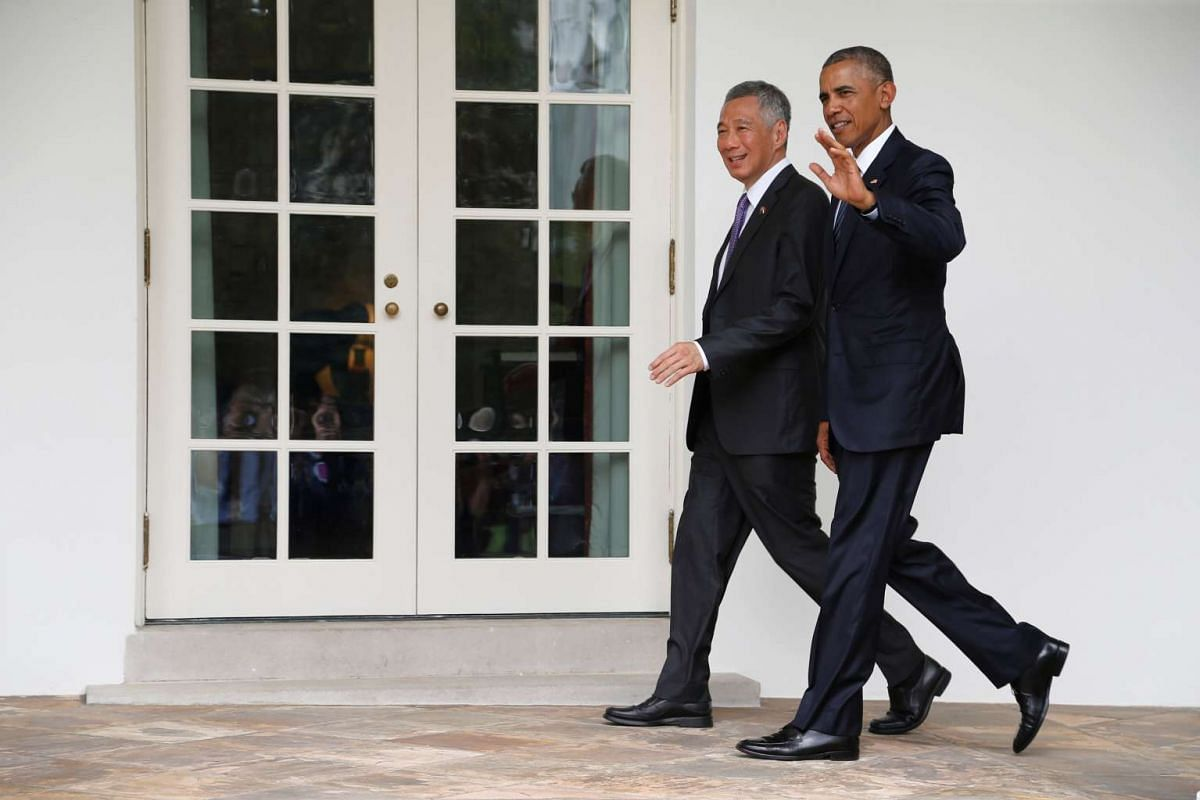 US President Barack Obama (right) and Singapore Prime Minister Lee Hsien Loong walk together to the Oval Office after an official arrival ceremony at the White House on August 2.