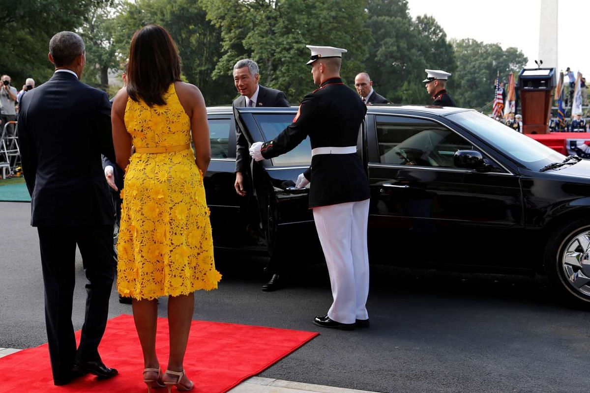 US President Barack Obama and first lady Michelle Obama greet Singapore's Prime Minister Lee Hsien Loong as he arrives for an official arrival ceremony on the South Lawn of the White House on August 2.