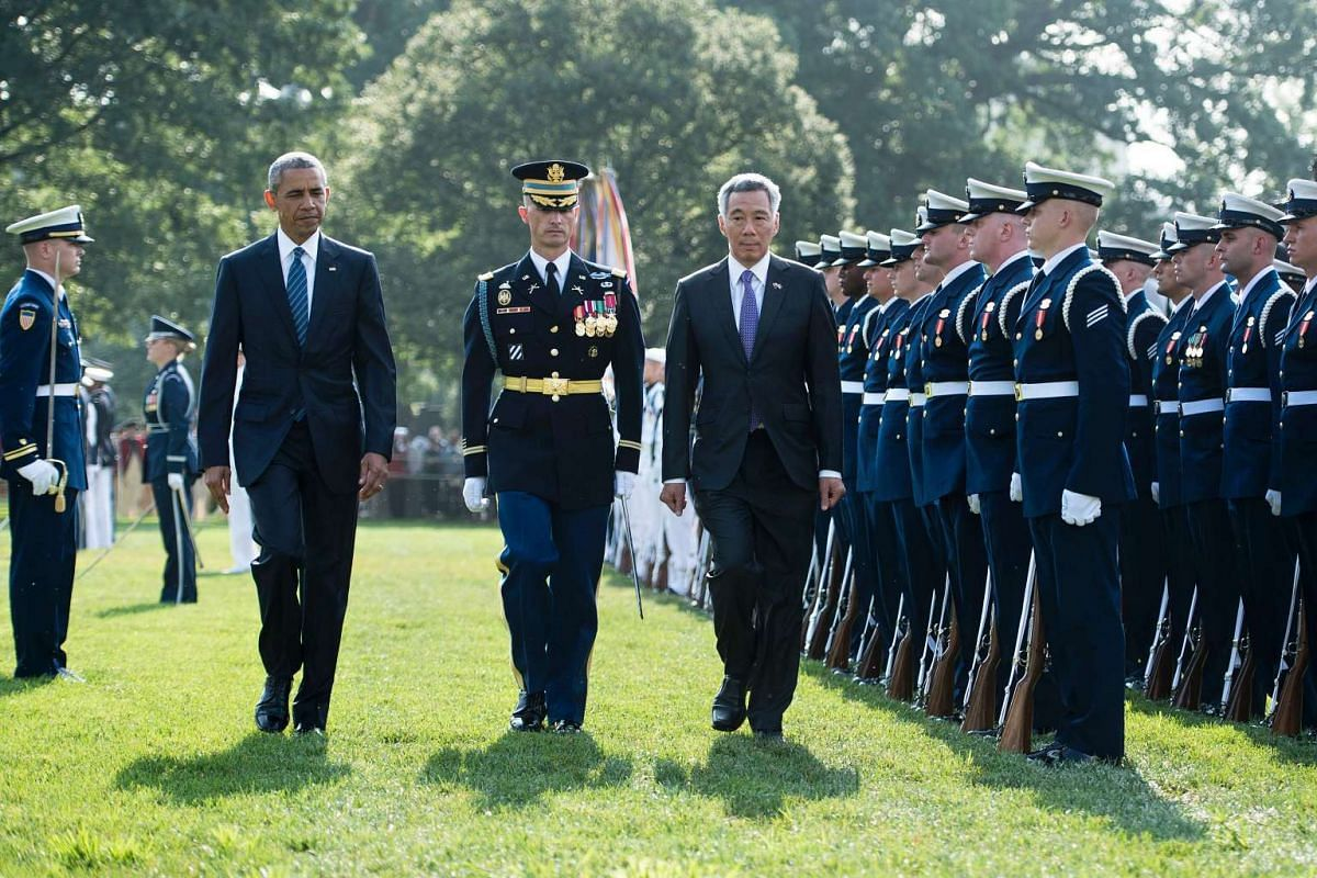 US President Barack Obama (left) and Singapore Prime Minister Lee Hsien Loong (right) inspect troops during an arrival ceremony on the South Lawn of the White House on August 2 in Washington, DC.