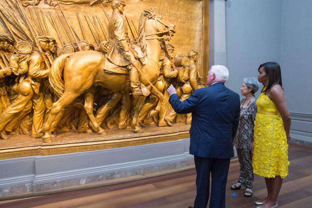 """First Lady Michelle Obama and Mrs Lee Hsien Loong look at the Shaw Memorial as they are escorted through the National Gallery of Art in Washington DC on August 2 by Museum Director Earl """"Rusty"""" Powell III."""