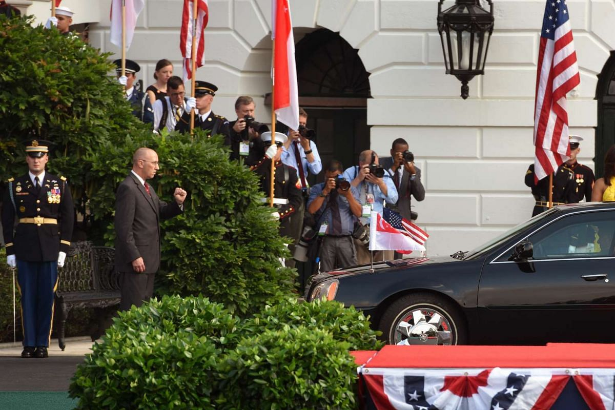 Photographers stack up on the staircase to witness the arrival of Singapore's Prime Minister Lee and Mrs Lee in his motorcade on August 2.