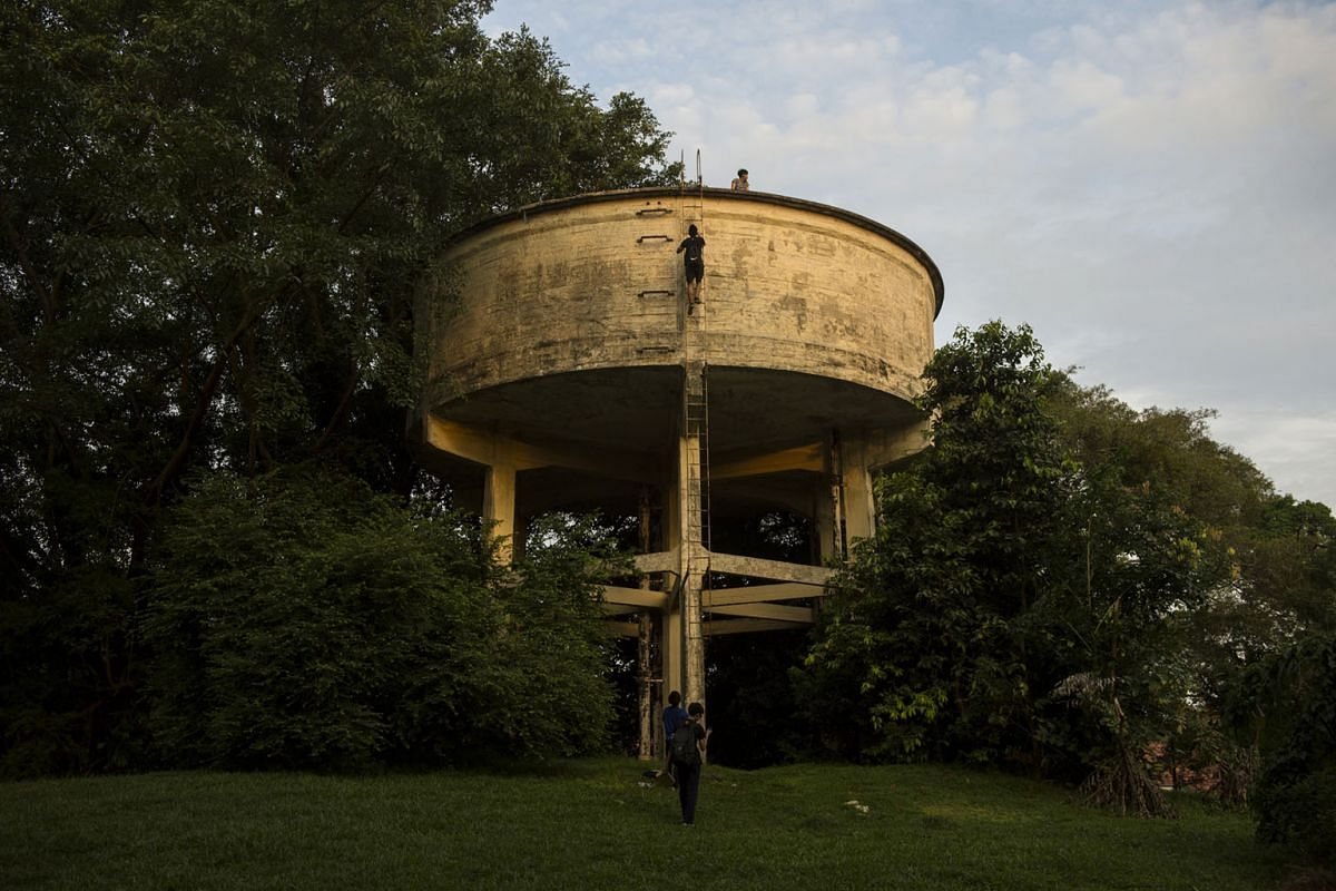 Schoolboys scale a rusty metal ladder leading to the top of an abandoned water tank. Like a giant cake on stilts, the UFO-like structure is nestled in vegetation on a small hill in between iconic colonial-style properties, which used to house British sold