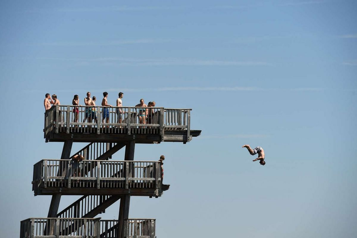 A boy jumps from a diving tower on the shore of the lake Ammersee near the small Bavarian village Utting, southern Germany, on August 4.