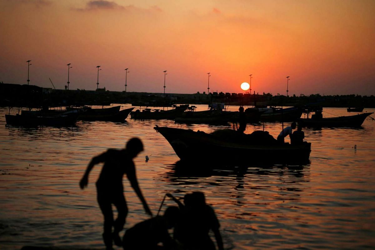 Palestinian boys prepare a fishing net during sunset at the seaport of Gaza City on August 4.