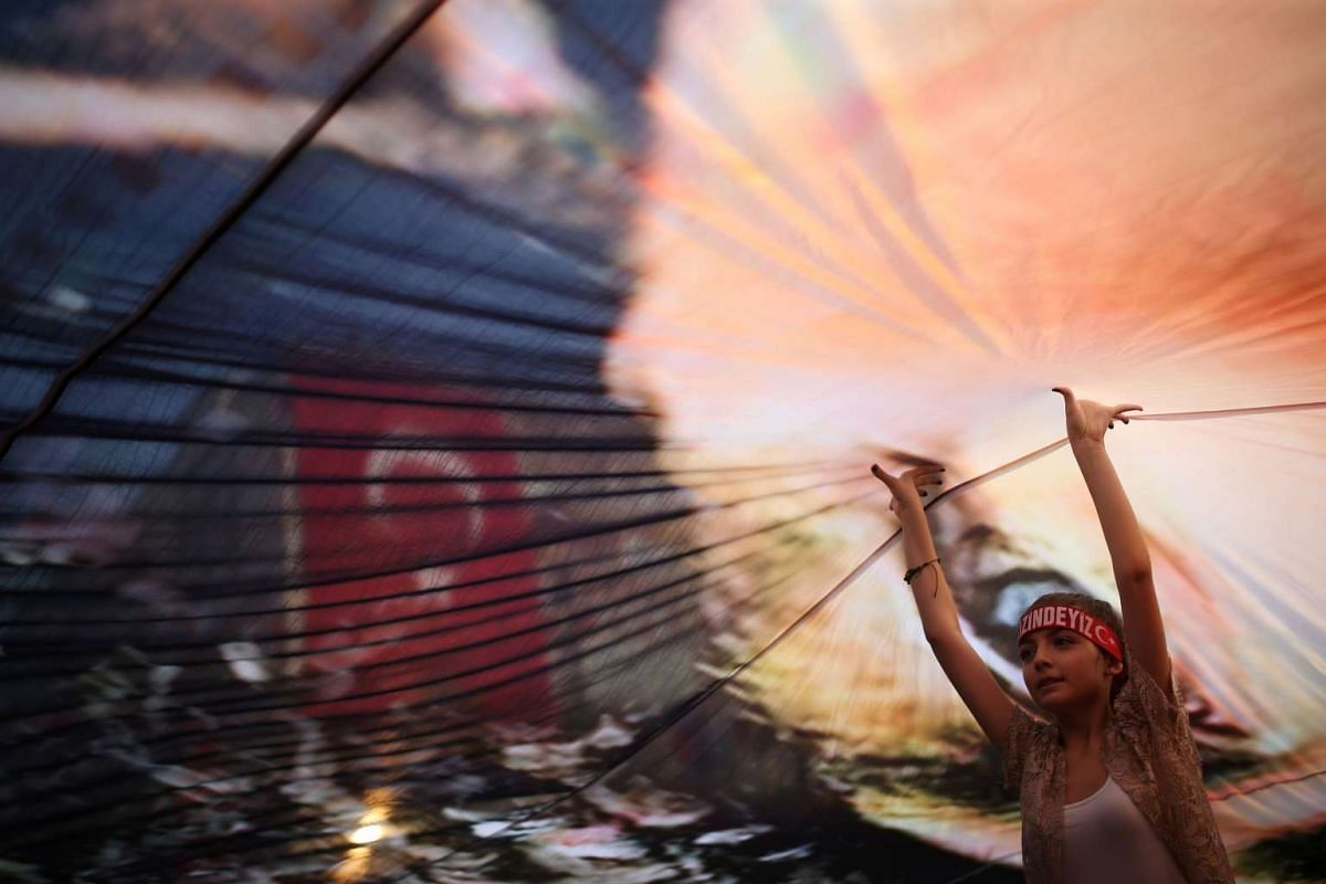 A Turkish girl helps to hold up a huge picture of modern Turkey's founder Mustafa Kemal Ataturk at an anti-coup rally in Gundogdu Square in Izmir on August 4.