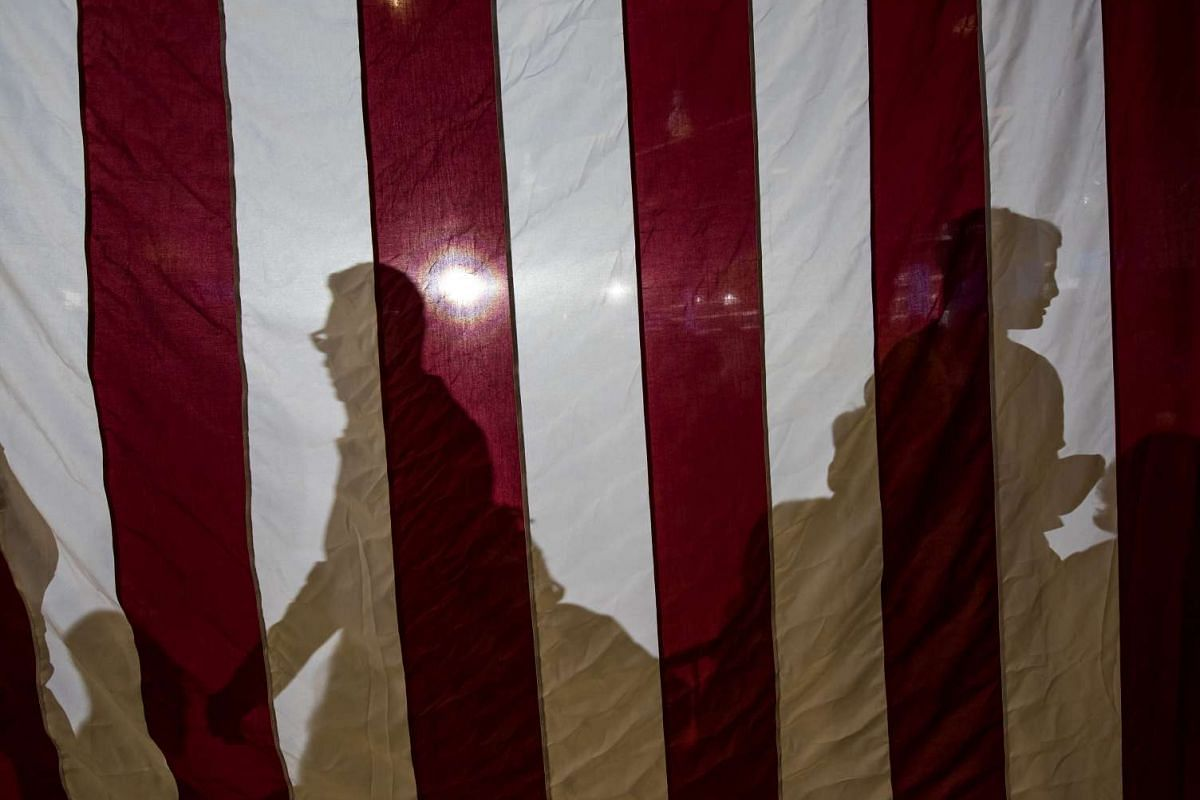 The shadows of attendees are seen on an American flag during a campaign event with Hillary Clinton in Las Vegas on August 4.