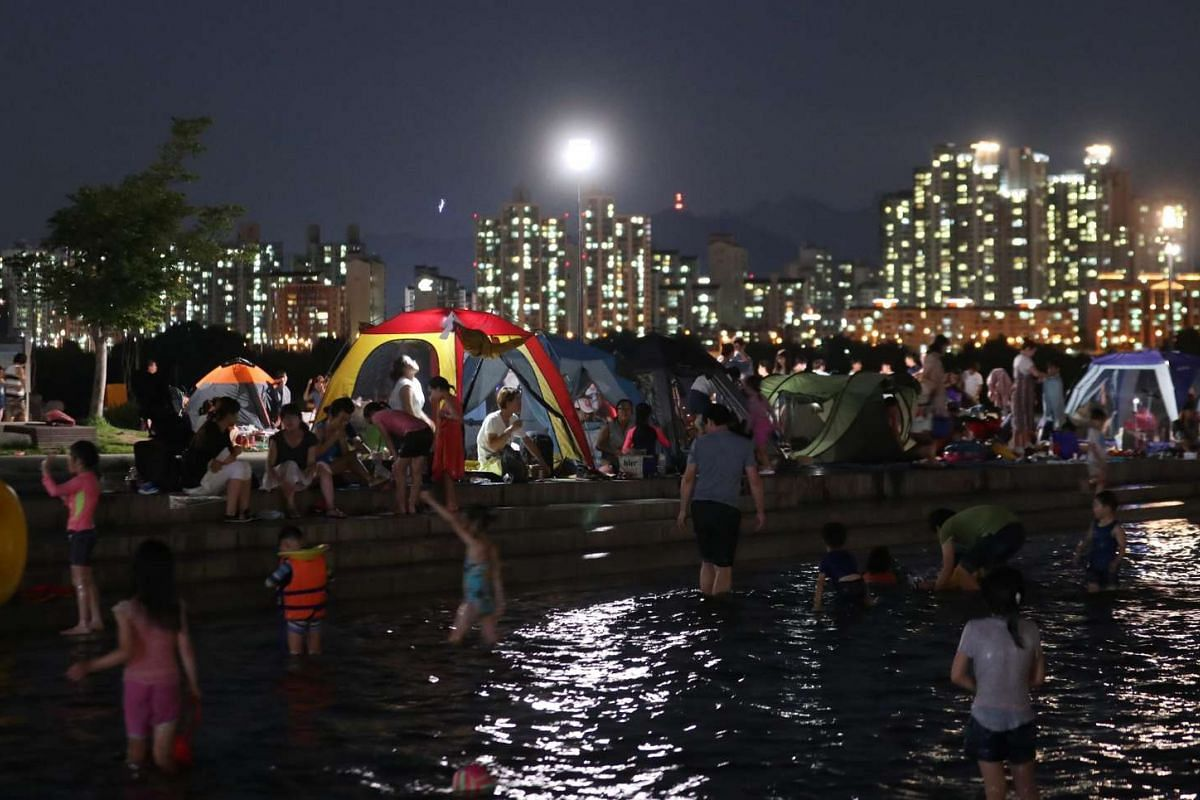People seek a reprieve from a hot summer night on August 4 at a Han River park in Seoul, South Korea.