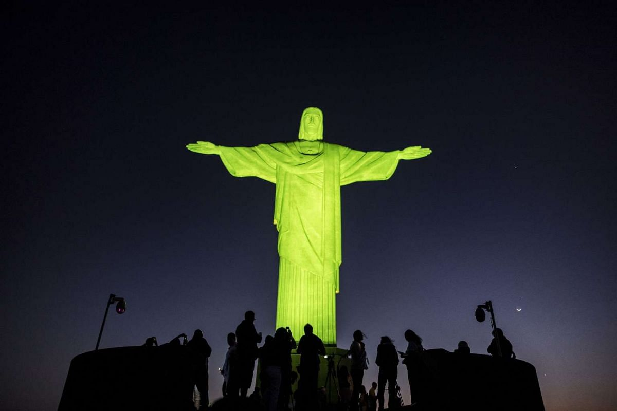 Visitors stand under the Christ the Redeemer statue on Corcovado mountain ahead of the Rio 2016 Olympic Games in Rio de Janeiro on August 4.
