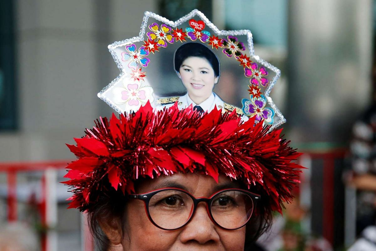 A supporter of former Thai Prime Minister Yingluck Shinawatra stands outside the Supreme Court in Bangkok, Thailand, August 5.