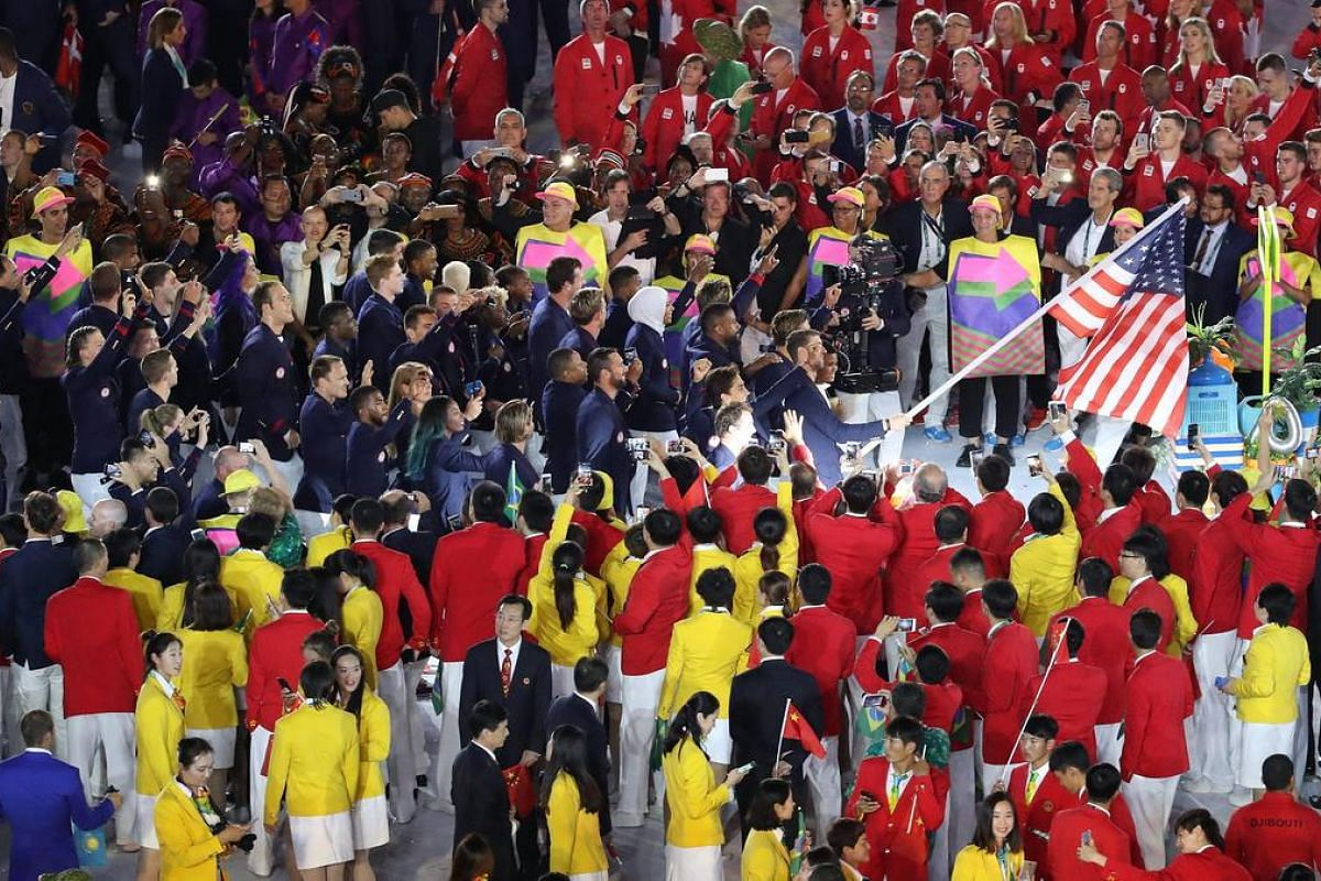 The US team led by flagbearer Michael Phelps arrives during the Opening Ceremony.