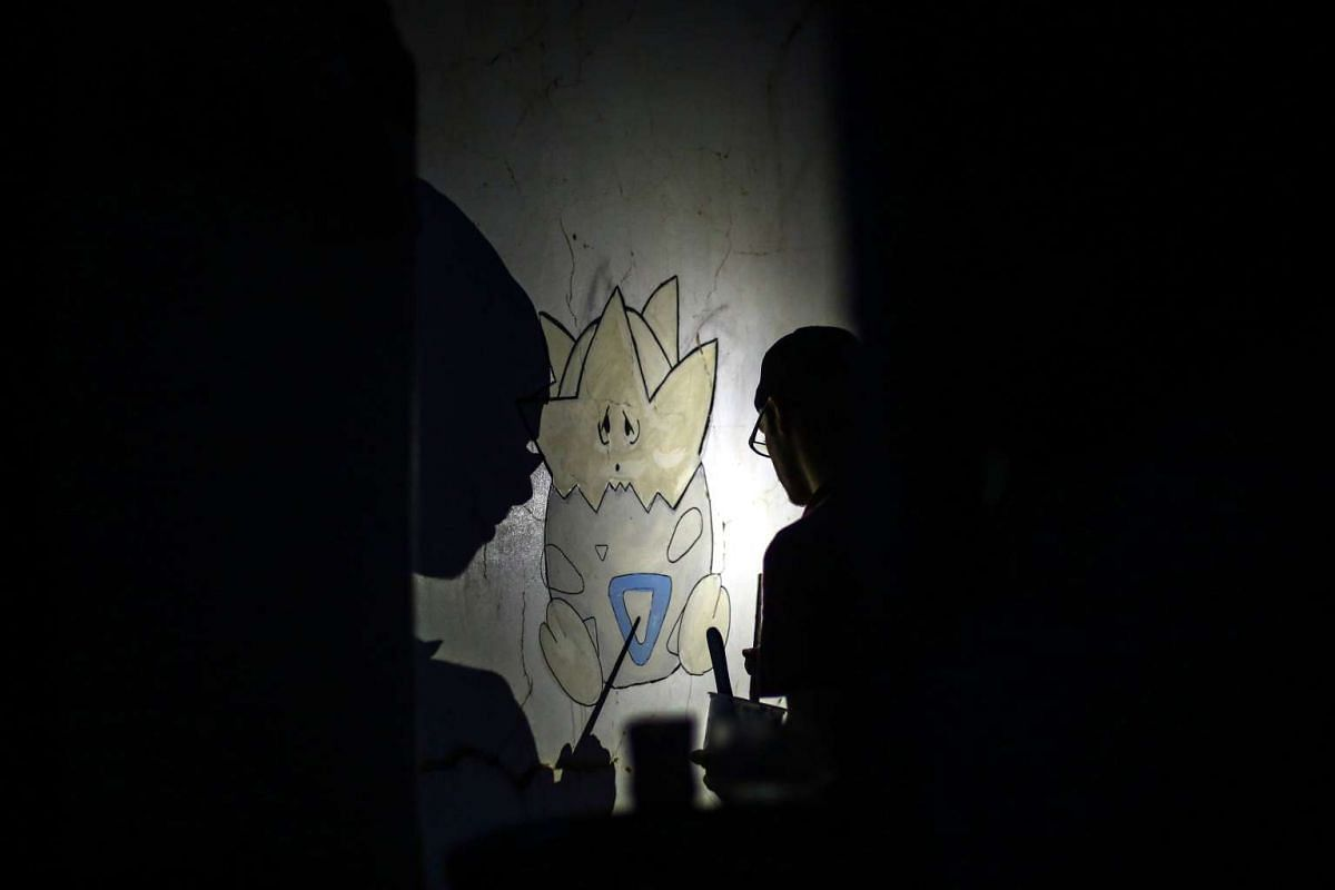 Syrian artist Omair Abd, 21, paints a Pokemon figure on the wall of a destroyed house in the rebel-held city of Douma, outskirts of Damascus, Syria,on July 31, 2016. Young activists want to raise awareness for the conflict by placing Pokemon monsters