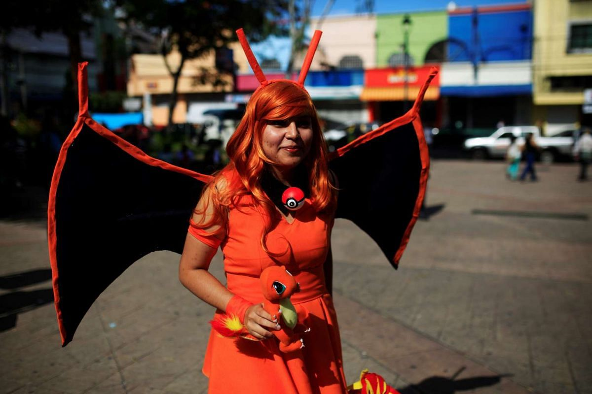 """Cosplayer dressed as a character of the augmented reality mobile game Pokemon Go by Nintendo participate in a """"poketour"""" organised by the municipality in San Salvador, El Salvador on July 23, 2016."""