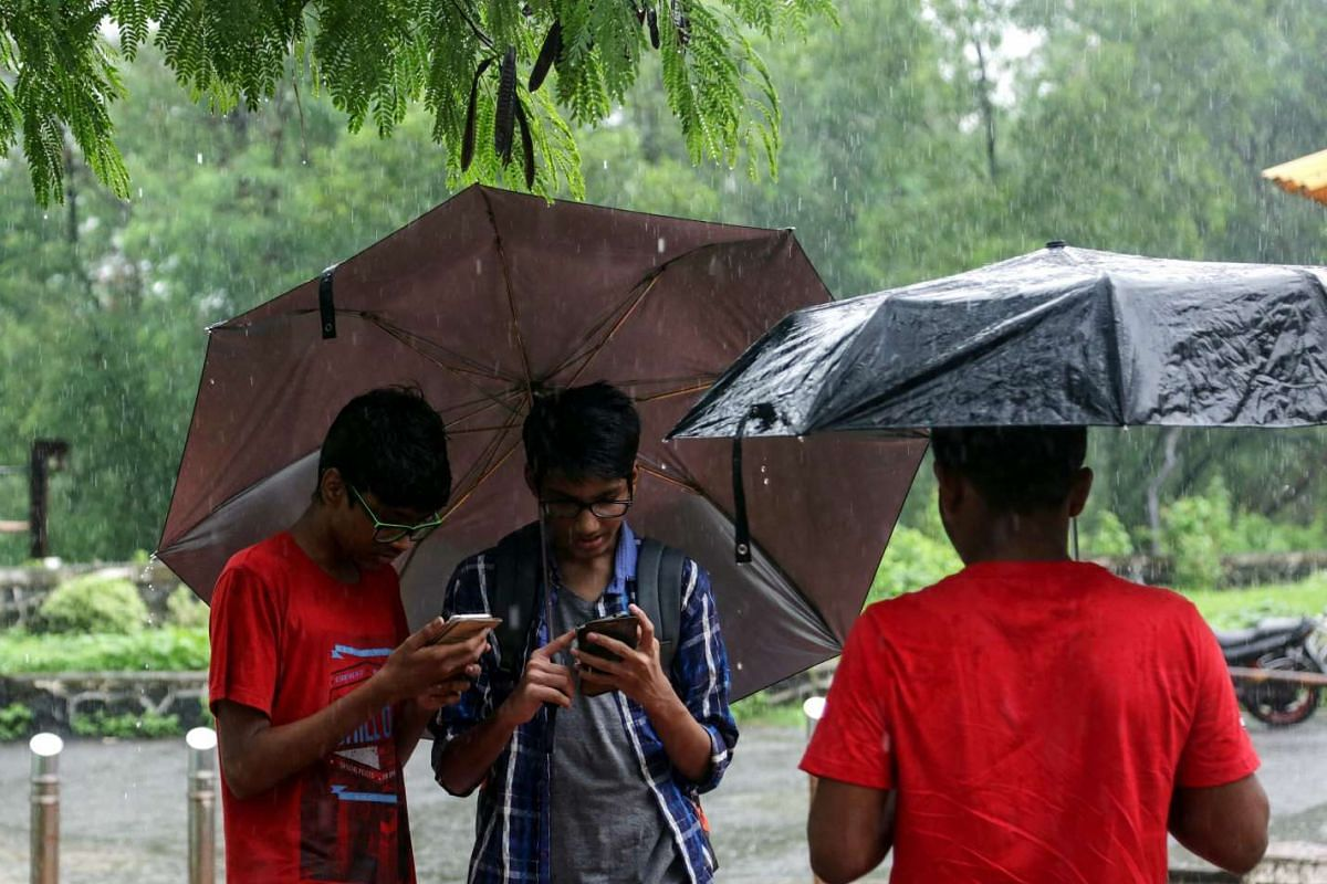 Enthusiasts hold umbrellas to protect themselves and their cell phones as they try to catch a Pokemon character during a rain shower in  Mumbai, on July 31, 2016. Although the game has not yet been officially launched there, many people have found wa