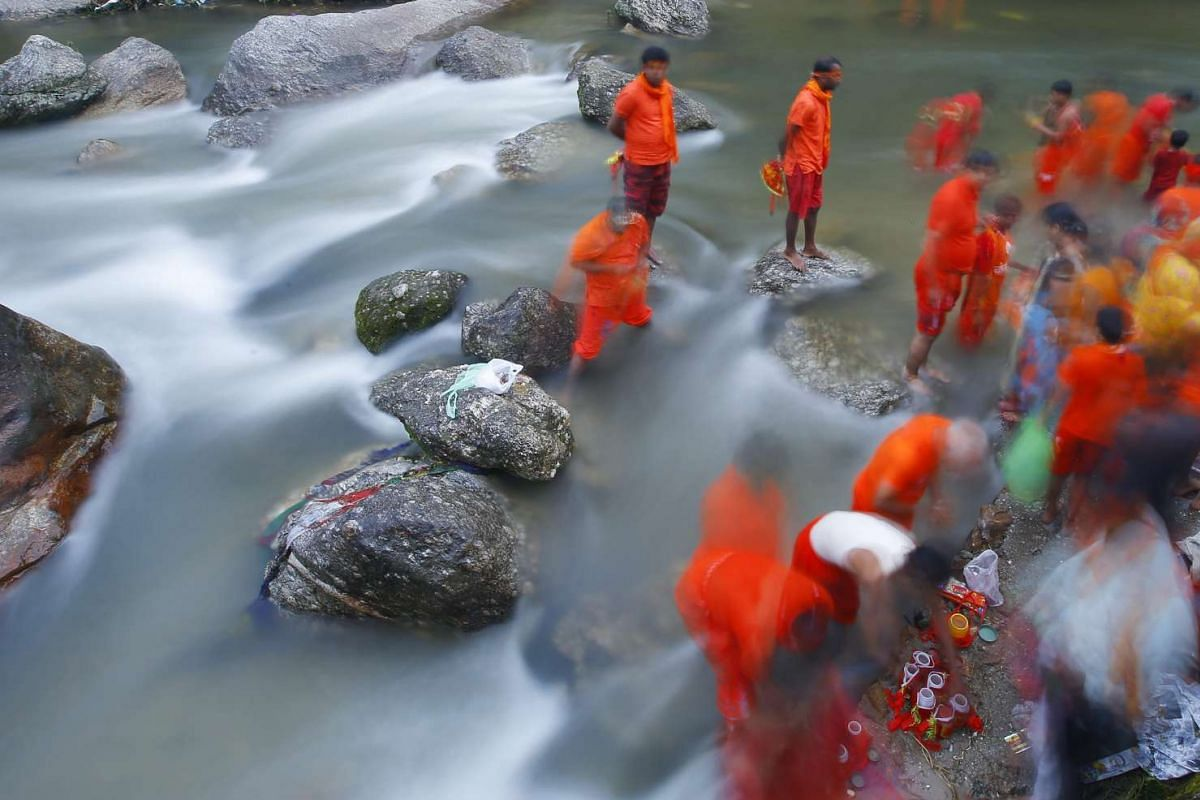 Nepalese Hindu pilgrims collecting holy water to worship Lord Shiva, the god of creation and destruction, at the Bagmati river in Kathmandu on Aug 8, 2016.