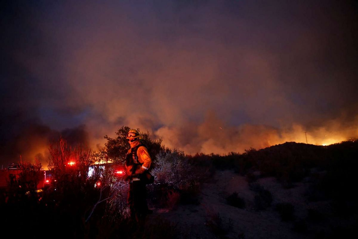 A firefighter watches as smoke clouds billow during the Pilot Fire near Silverwood Lake in San Bernardino county on Aug 7, 2016.
