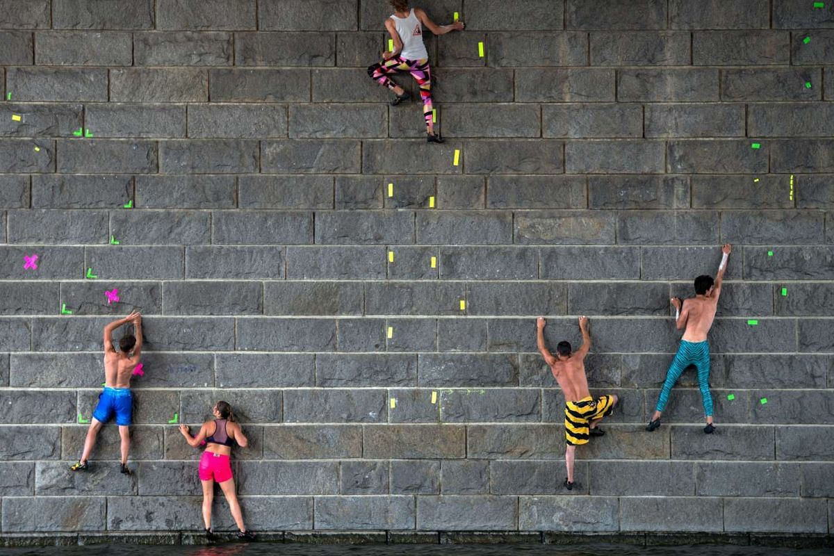 Participants climb up a prier of the Reichsbruecke over the Danube River during the 'Urban Waters Cup 2016' boulder competition in Vienna on Aug 6,  2016.