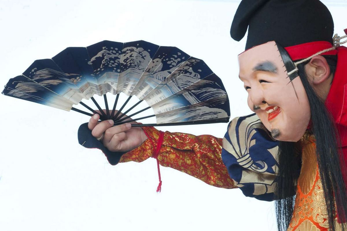 A Japanese performs as the god Ebisu during a Kagura trance dance performance by local teenagers in Gotsu city, on Aug 7, 2016.