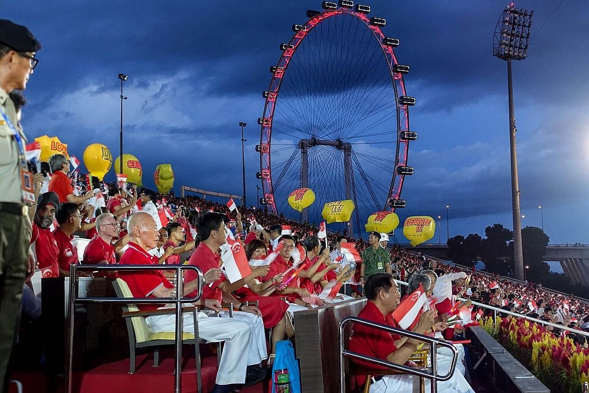 """Above: In 2014, at the Floating Platform, Prime Minister Lee turned back and saw his father """"watching the show, nearly 50 years after that first parade in 1966 that he had supervised, personally and in detail"""". It was to be Mr Lee Kuan Yew's last NDP"""