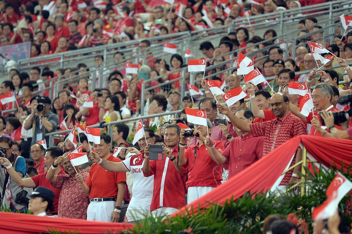Ministers, including PM Lee, stand up in the VIP box to greet the arrival of President Tony Tan Keng Yam.