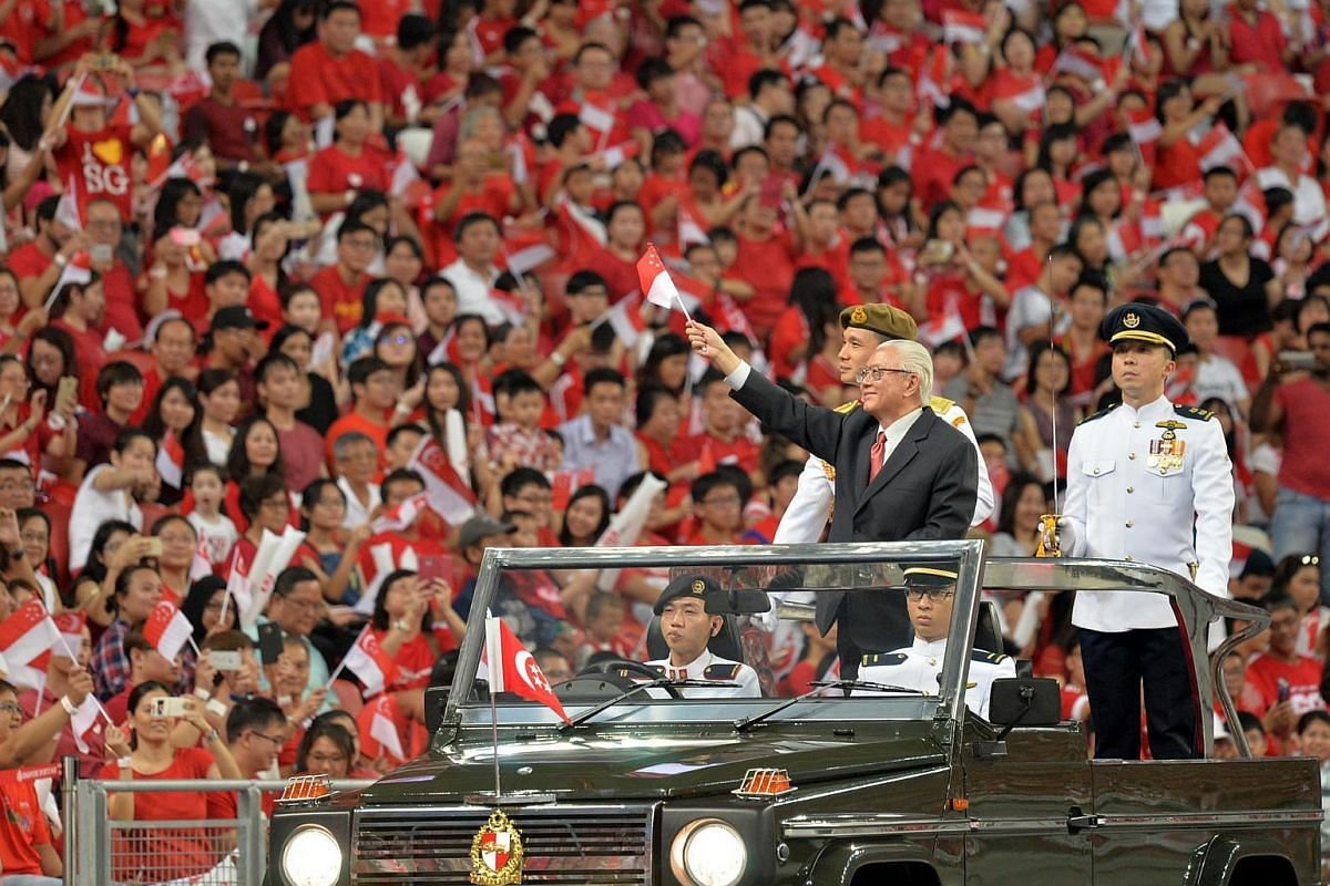 President Tan waves a Singapore flag as he greets the crowd during the drive-past.